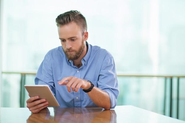 Ernstige zitting van de mens in cafe tafel en tablet met behulp van Gratis Foto