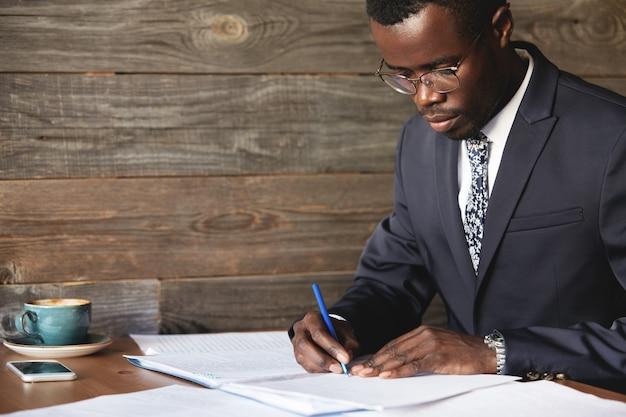 Ernstige zwarte bedrijfsmedewerker in formeel pak en bril die een lucratief contract ondertekent Gratis Foto