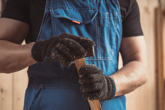 Ervaren timmerman in werkkleding en kleine bedrijfseigenaar die in houtbewerkingsworkshop werkt Premium Foto