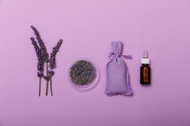 Essentiële lavendelolie en bloem met kleine zak op paars. Premium Foto