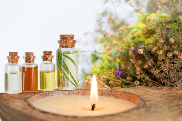 Essentiële oliën spa set met brandende kaars, gezonde kruiden en bloem Premium Foto