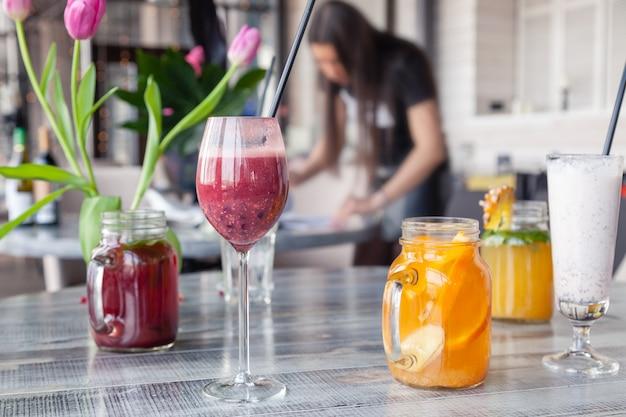 Eten stylist en fotograaf versieren, het voorbereiden om verschillende cocktails, milkshakes, smoothies, vaas met bloementulpen op tafel te schieten. Premium Foto