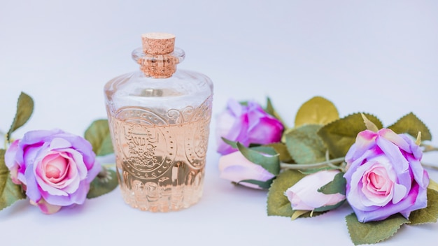 Etherische oliefles en valse bloemen op witte oppervlakte Gratis Foto