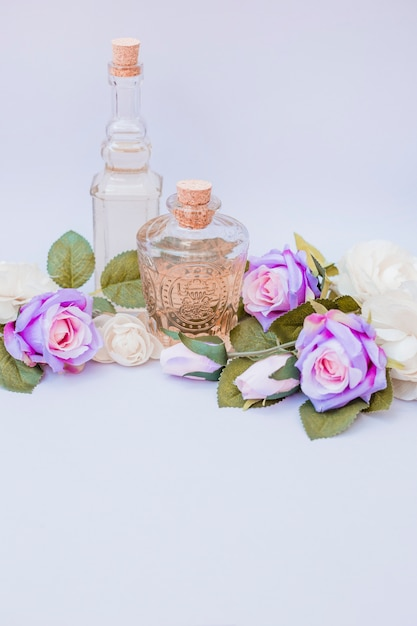 Etherische olieflessen en valse rozen op witte achtergrond Premium Foto