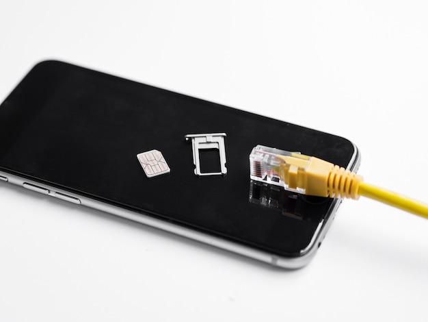 Ethernetkabel en simkaart bovenop telefoon Gratis Foto