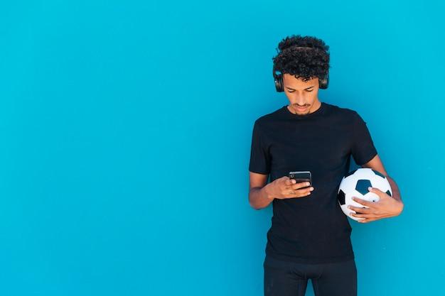 Etnische krullende atleet houdt voetbal en het gebruik van de telefoon Gratis Foto