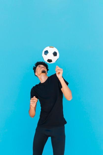 Etnische man met krullend haar spelen met voetbal Gratis Foto