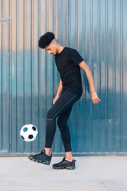 Etnische sportman schoppen voetbal op straat Gratis Foto