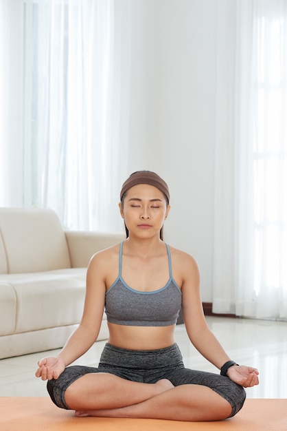 Etnische sportvrouw thuis mediteren Gratis Foto