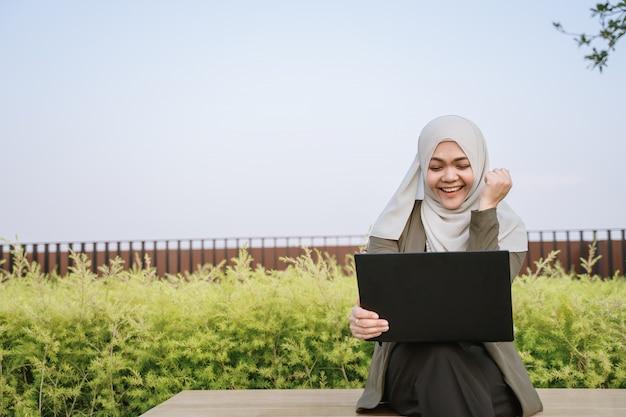 Euphoric winnaar aziatische moslimvrouw in groene pak en werken op een computer in het park. Premium Foto