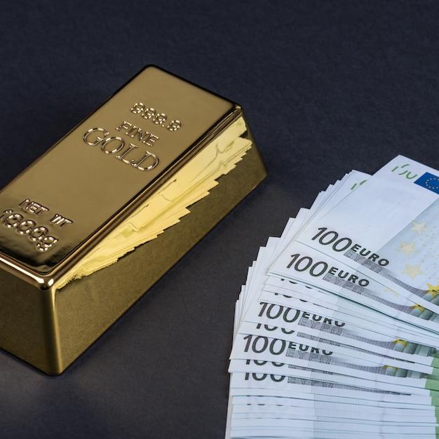 Euro contant geld en gouden staaf op een zwarte achtergrond. bankbiljetten. geld. bill. ingot. bullion. Premium Foto