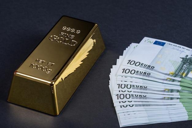 Euro contant geld en goudstaaf op zwart Premium Foto