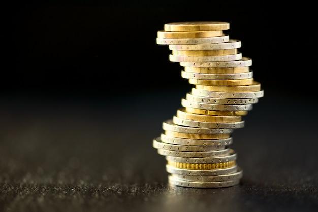 Euro geld, valuta. succes, rijkdom en armoede, armoedeconcept. euro-munten stapel op donker zwart met kopie ruimte. Premium Foto