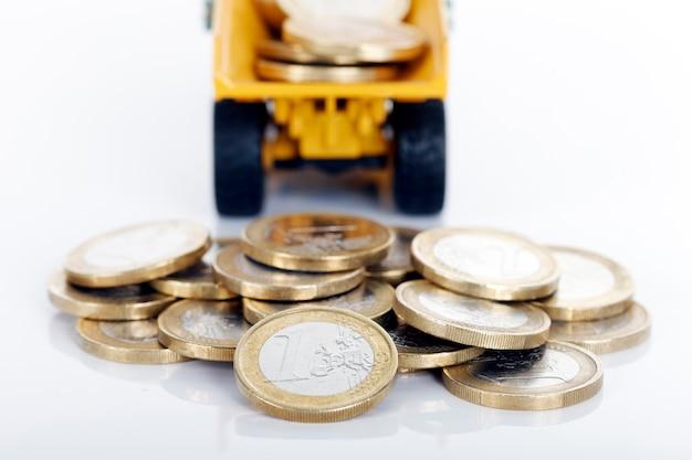 Euro geldmunten en vrachtwagen op witte ruimte Gratis Foto