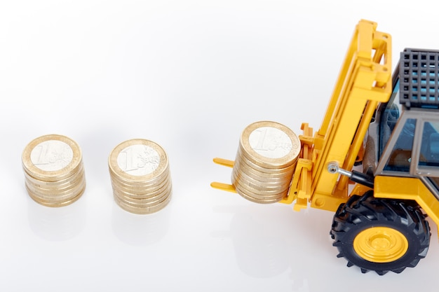 Eurogeldmunten en vorkheftruck op witte ruimte Gratis Foto
