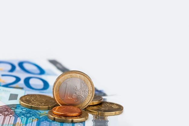 Euromunten en bankbiljetten met een vel papier en pen Premium Foto