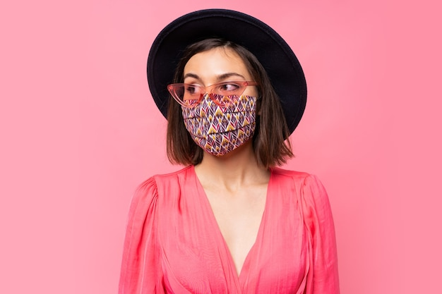 Europees model gekleed beschermend stijlvol gezichtsmasker. zwarte hoed en zonnebril dragen. poseren over roze muur Gratis Foto