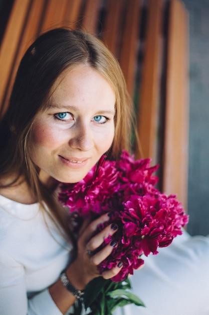 Europees uitziende meisje met bloemen, pioenrozen in haar handen Premium Foto