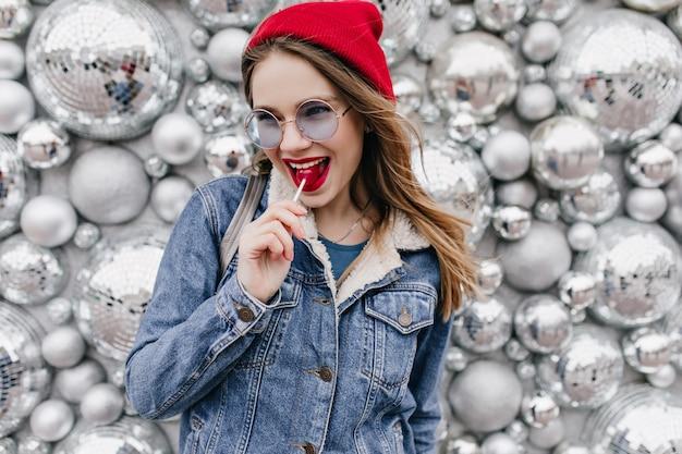Europese vrouw in spijkerjasje speels poseren met lolly. extatisch meisje met lichtbruin haar met snoep op fonkelingsmuur. Gratis Foto