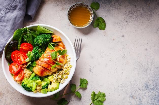 Evenwichtig voedselconcept. kip, broccoli en quinoa salade in witte kom, grijze achtergrond, bovenaanzicht. Premium Foto