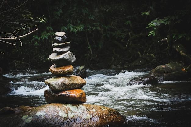 Evenwichtige stenen pyramide op de oever van water val van bergmeer. blauwe bergen in waterspiegelspiegel. slechte lichtomstandigheden. Premium Foto