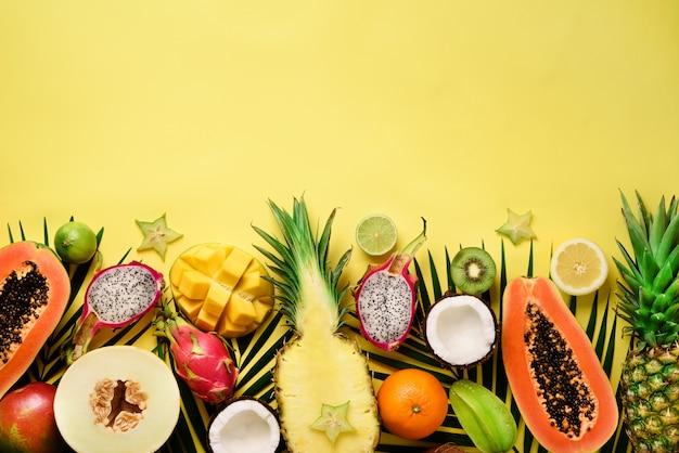 Exotisch fruit en tropische palmbladeren - papaja, mango, ananas, banaan, carambola, drakenfruit, kiwi, citroen, sinaasappel, meloen, kokosnoot, limoen. Premium Foto
