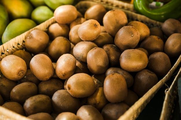 Exotische heerlijke organische kiwi in rieten mand bij markt Gratis Foto