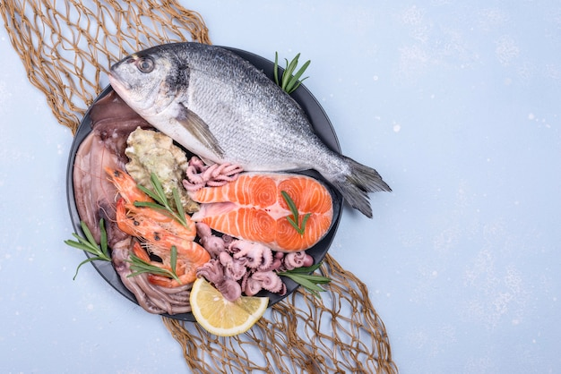 Exotische zeevruchtenschotel in een plaat en visnet bovenaanzicht Premium Foto