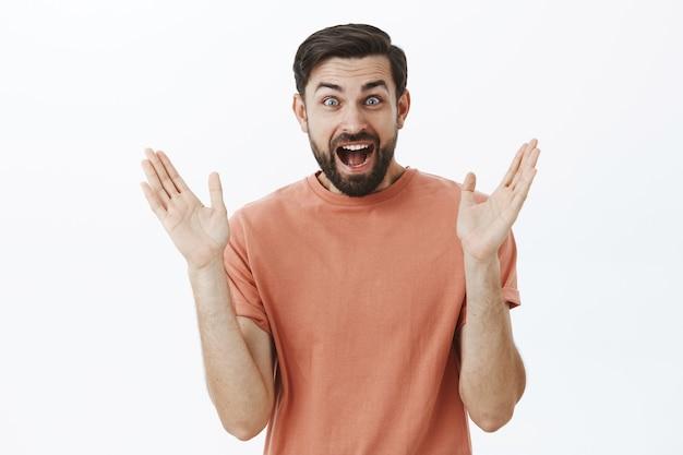 Expressieve bebaarde man in oranje t-shirt Gratis Foto