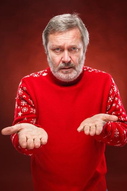 Expressieve man in rode kerst trui Gratis Foto