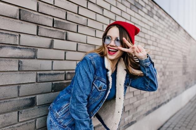 Extatisch meisje in het grappige stellen van de denimuitrusting dichtbij bakstenen muur in de lentedag. portret van vrolijk kaukasisch vrouwelijk model dat zich op straat met vredesteken bevindt. Gratis Foto
