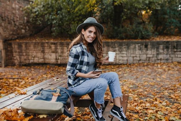 Extatische blanke vrouw in vintage jeans, zittend op een houten bankje in de herfstdag Gratis Foto