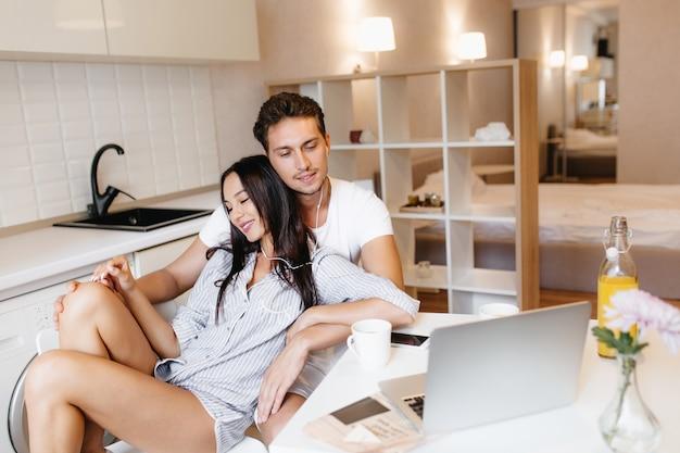 Extatische donkerharige vrouw in mannelijk blauw shirt chillen met vriendje in gezellige flat luisteren muziek Gratis Foto