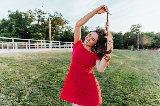 Extatische jonge dame in zomerkleding spelen met haar haren tijdens fotoshoot in park. buiten schot van schattig meisje in een rode jurk met plezier in weekend. Gratis Foto