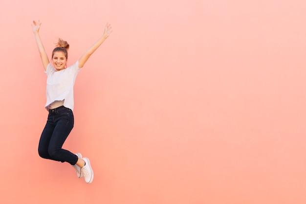 Extatische jonge vrouw die met haar die wapens springen tegen perzik gekleurde achtergrond worden opgeheven Gratis Foto