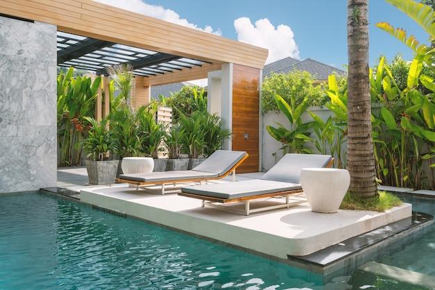 Exterieurontwerp van huis, huis, villa met ligstoel en met blauwe lucht en groene planten Premium Foto