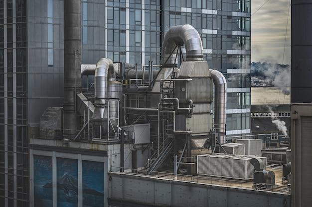 Fabriek omgeven door hoogbouw met groen Gratis Foto