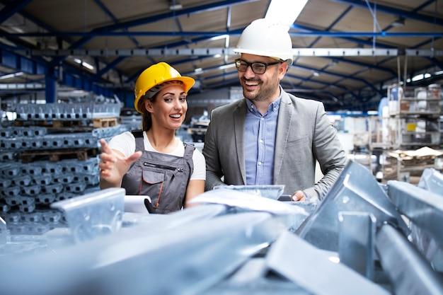 Fabrieksarbeider draagt veiligheidshelm en uniform tonen nieuwe metalen producten aan de manager supervisor Gratis Foto