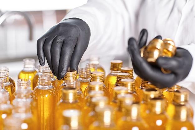 Fabrieksarbeider in witte jurk en rubberen handschoenen die kroonkurken schroeven Gratis Foto