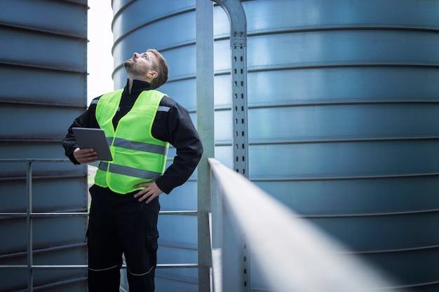 Fabrieksarbeider staande op metalen platform tussen industriële opslagtanks en op zoek naar visuele inspectie van silo's voedselproductie Gratis Foto