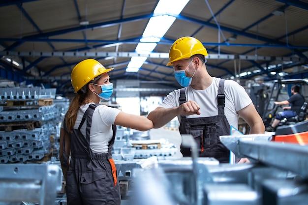 Fabrieksarbeiders begroeten elkaar met ellebogen tijdens pandemie van het coronavirus Gratis Foto