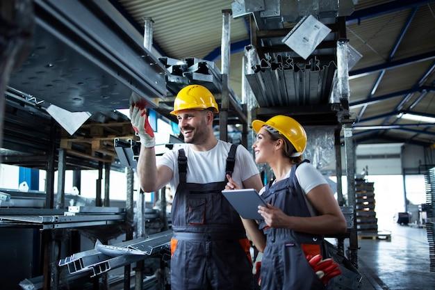 Fabrieksarbeiders inventariseren met tabletcomputer in industrieel magazijn vol metalen onderdelen Gratis Foto
