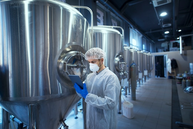 Fabrieksarbeidertechnoloog in beschermend uniform met haarnetje en masker dat de voedselproductie op tabletcomputer controleert Gratis Foto