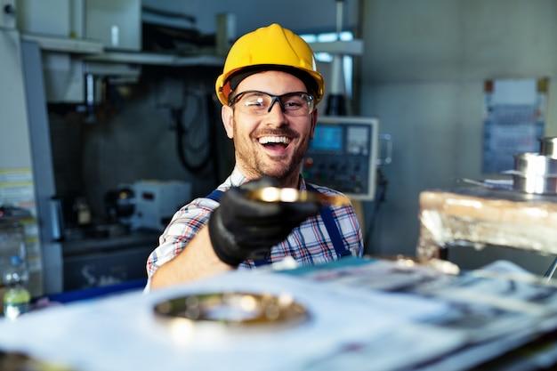 Fabrieksingenieur controleert de kwaliteit van het vervaardigde onderdeel Premium Foto