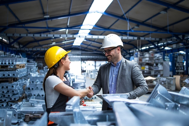 Fabrieksmanager die de productielijn bezoekt en de werknemer feliciteert met promotie voor hard werken en goede resultaten Gratis Foto
