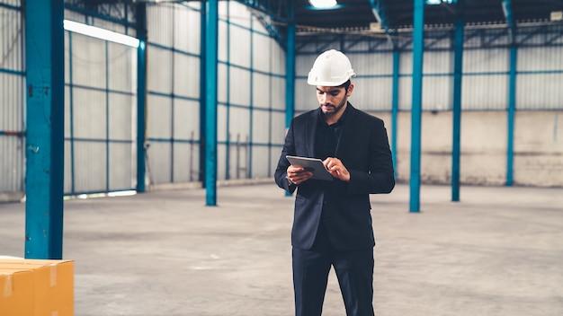 Fabrieksmanager met behulp van tabletcomputer in magazijn of fabriek Premium Foto