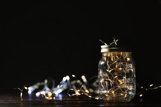 Fairy licht in een glazen pot. kerstmis / gelukkig nieuwjaar decoratie achtergrond. Premium Foto