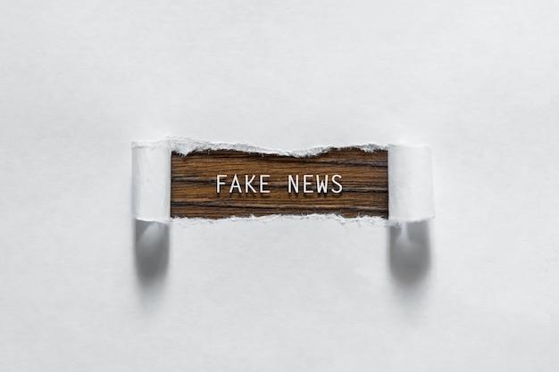 Fake news - een inscriptie in een gescheurd wit papier Premium Foto