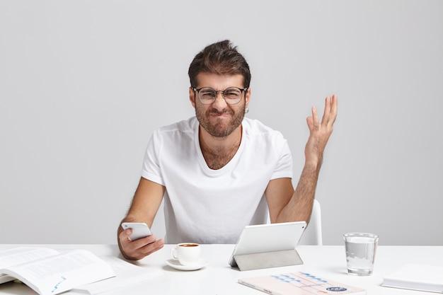 Falen, zenuwinzinking en stress op het werk. stressvolle boze jonge europese manager met baard grimassen en gebaren Gratis Foto