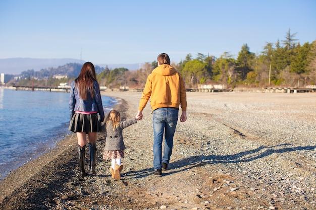 Familie bij wild strand tijdens de warme winter Premium Foto